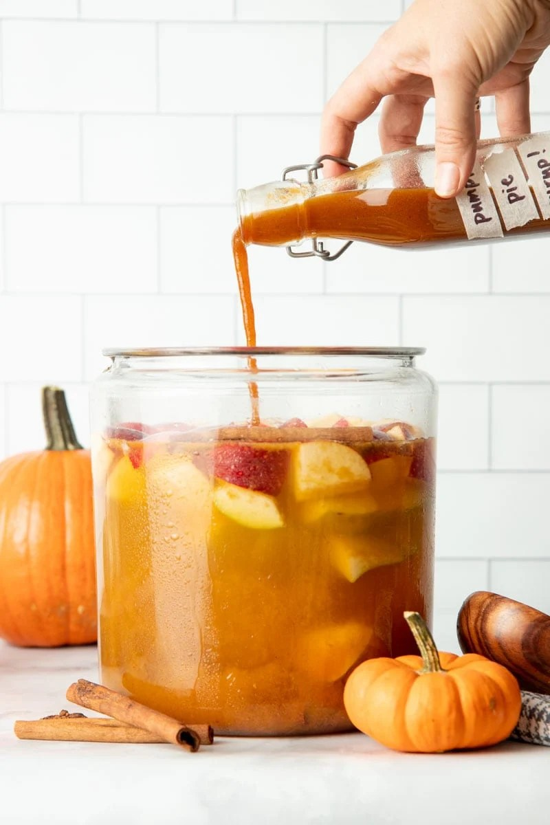 A hand pours pumpkin spice syrup into a large pitcher.