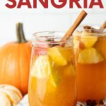 "Two glasses of pumpkin sangria sit on a kitchen linen surrounded by pumpkins and whole spices. A text overlay reads, ""Pumpkin Pie Sangria."""