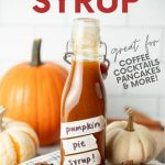 "A flip-top glass bottle filled with pumpkin spice syrup sits among decorative pumpkins, cinnamon sticks, and whole star anise. A text overlay reads, ""Pumpkin Pie Syrup. Great for Coffee, Cocktails, Pancakes, & More!"""