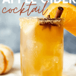 "Chilled glass of spiked cider filled with with ice and garnished with sugar rim, cinnamon stick, star anise pod, and orange slice. A text overlay reads, ""Bourbon Apple Cider Cocktail."""