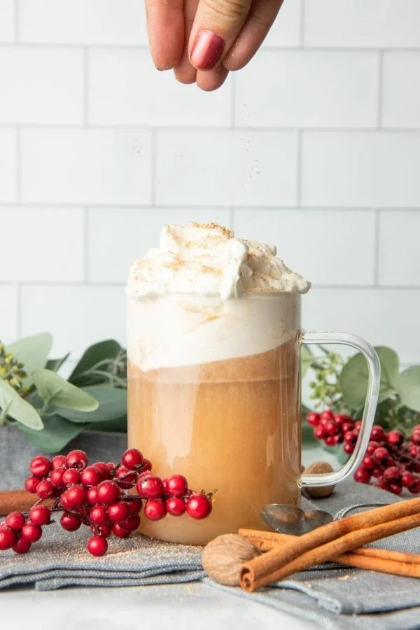 A hand sprinkles a pinch of nutmeg over the whipped cream topping a mug of hot buttered rum.