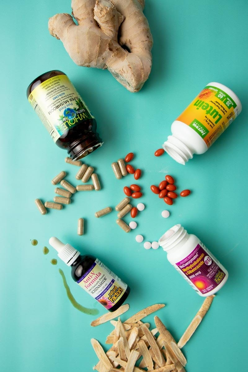 Herbal supplement bottles displayed with their pills, capsules, and droppers alongside all natural ingredients such as ginger root.