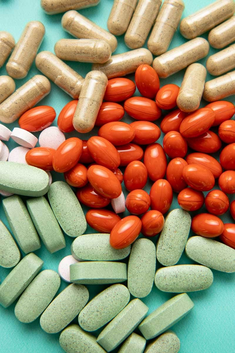 Close-up of four different varieties of herbal supplement pills and capsules.