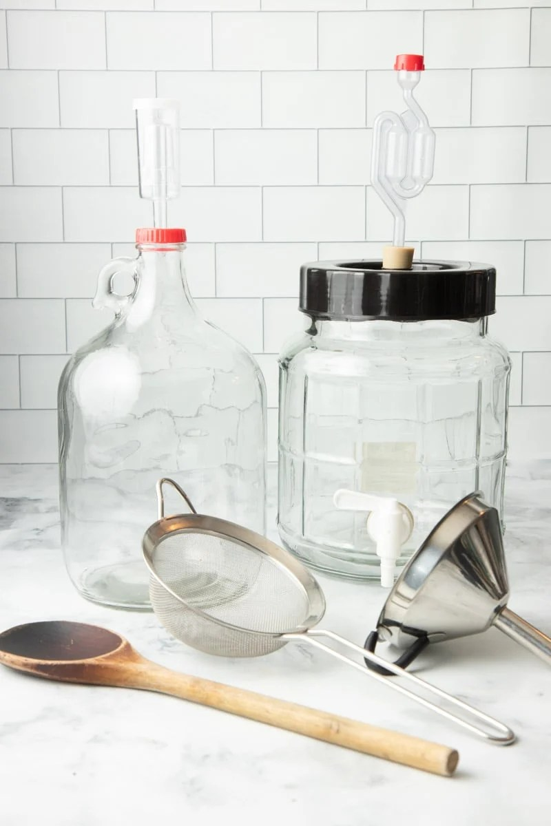Tools for making fruit wine at home such as wooden spoon, fine mesh strainer, funnel, glass fermenters, and air locks.