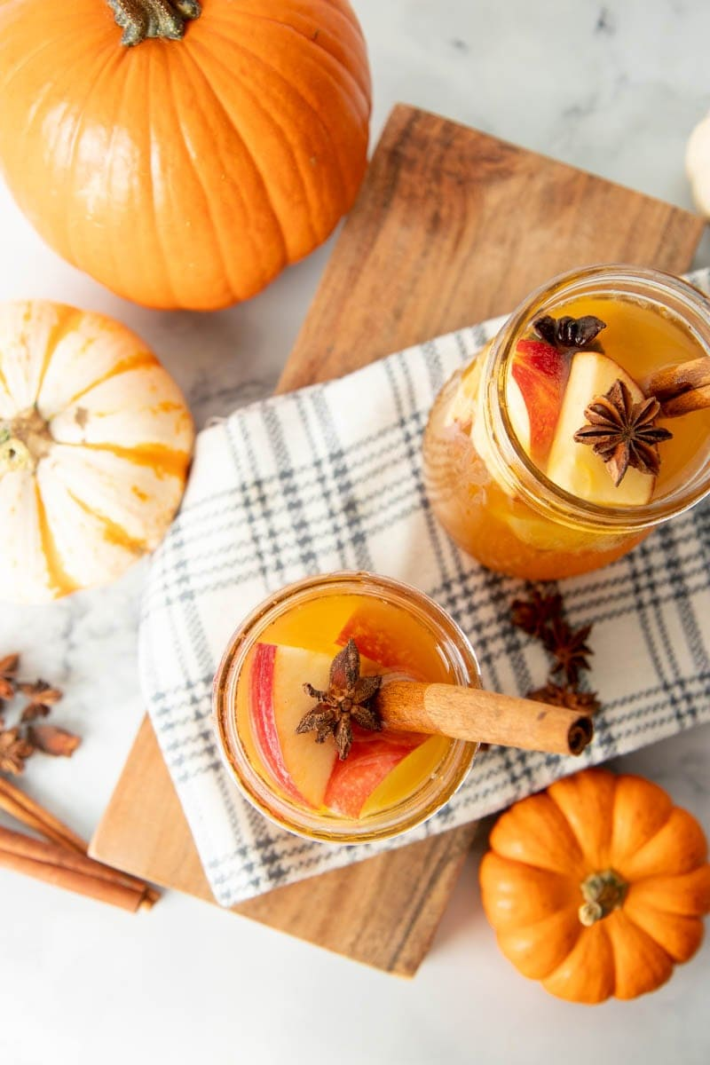 Overhead of two full glasses of pumpkin pie sangria garnished with cinnamon sticks and star anise pods.