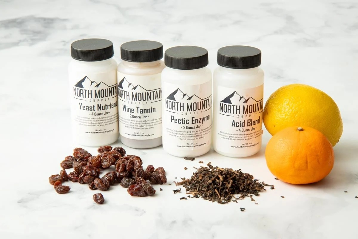 Bottles of wine additives from North Mountain Supply such as yeast nutrients, wine tannin, pectic enzyme, and acid blend along with fresh additives like raisins, citrus, and tea.