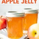 "Two Ball Smooth Sided Half Pint Jars of canned apple jelly sit next to fresh apples. A text overlay reads, ""How to Can Apple Jelly."""