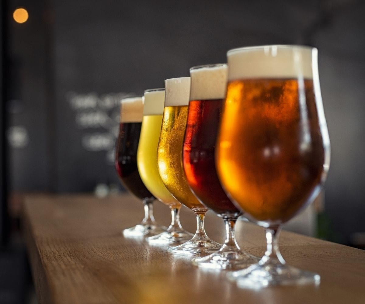 Five tulip beer glasses lined up along a bar and filled with beers in different hues.
