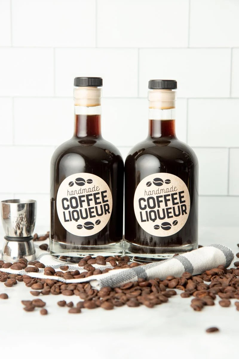 Two glass bottles of homemade Kahlua stand side-by-side surrounded by coffee beans.