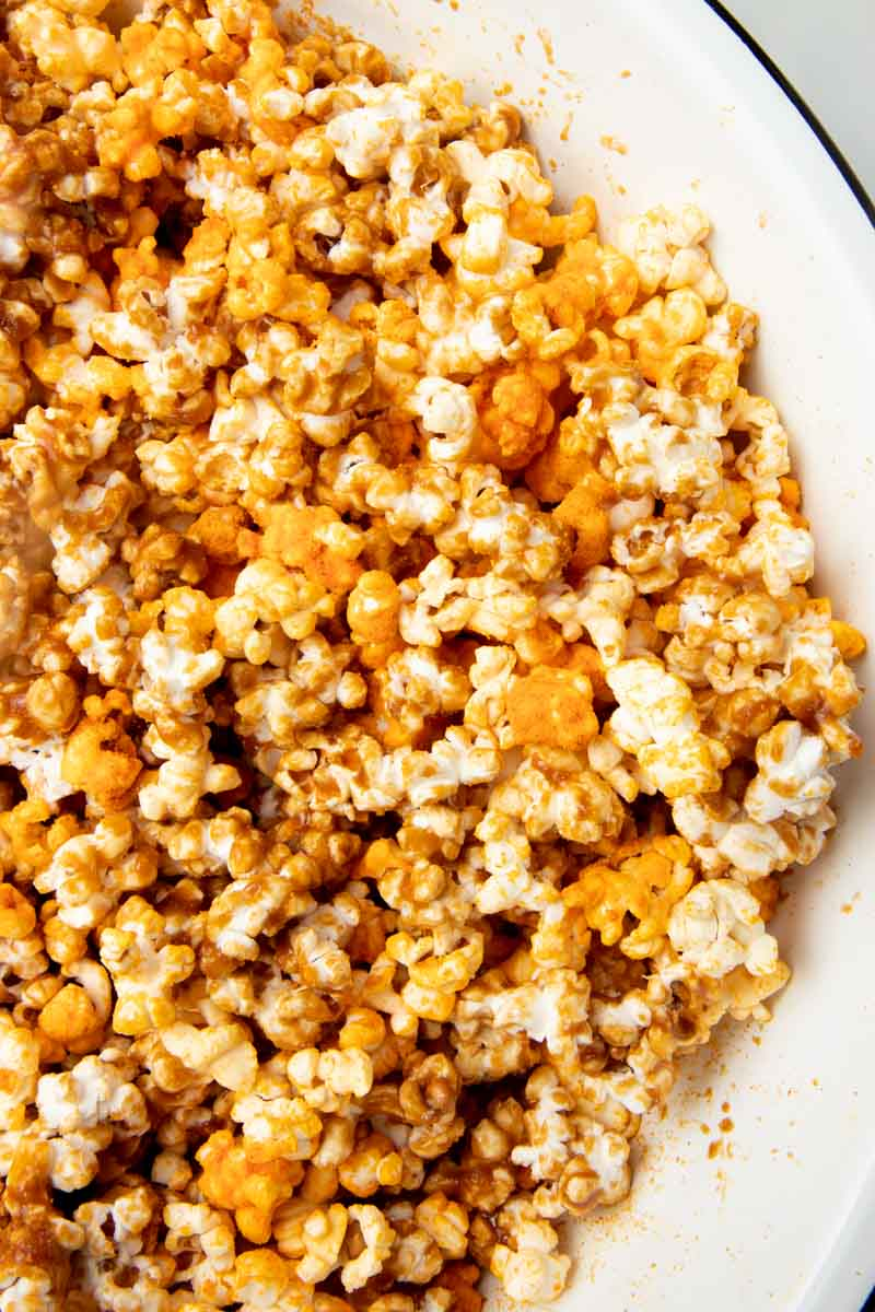 Homemade cheese and caramel popcorn mixed together in a large mixing bowl.