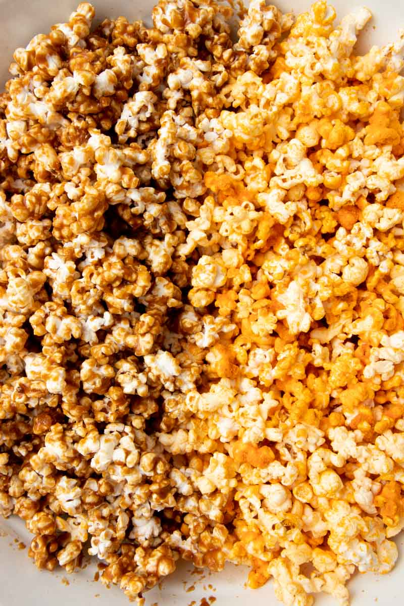 Homemade cheese and caramel popcorn side by side in a large mixing bowl.