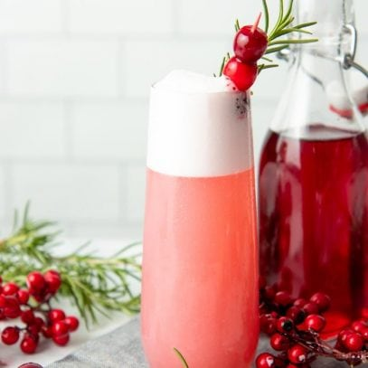 A mixed cranberry gin fizz cocktail stands beside an open flip-top bottle of cranberry simple syrup.