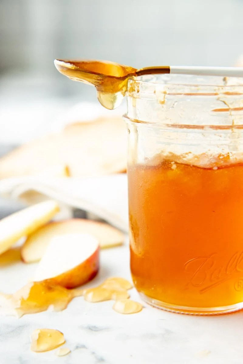 A spoon dripping apple jelly rests across the top of a jar of finished jelly.