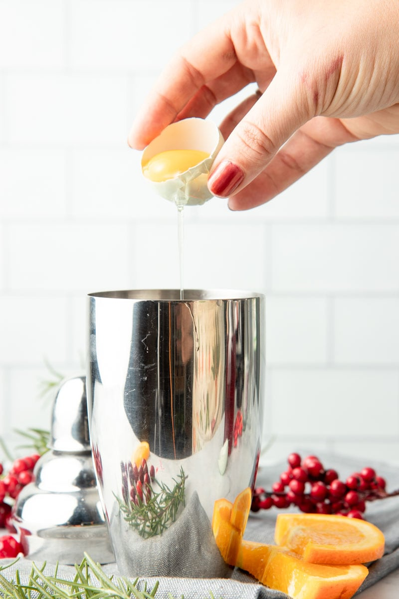 A hand pours an egg white from an eggshell into a cocktail shaker.