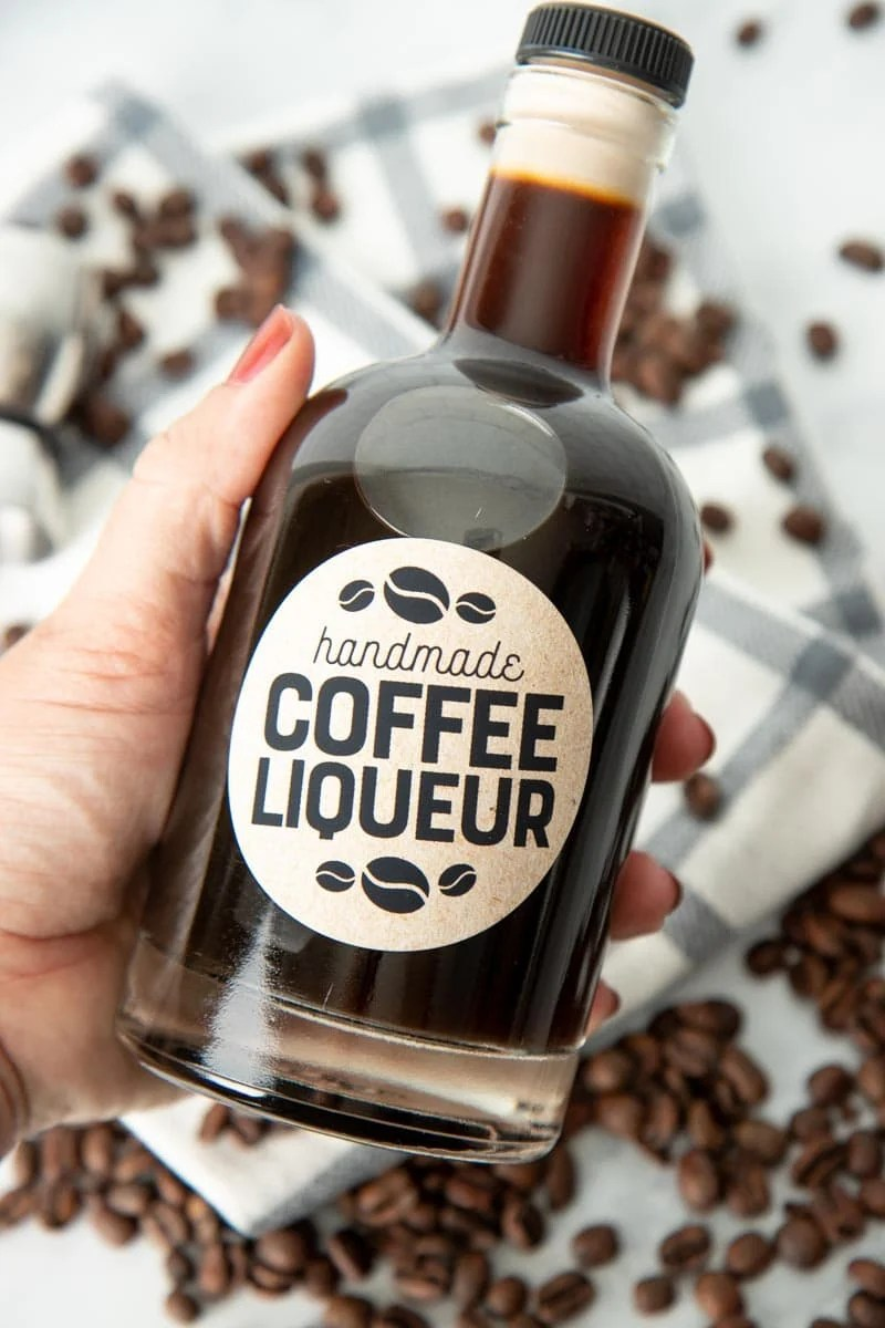 A hand holds a glass bottle filled with homemade coffee liqueur.