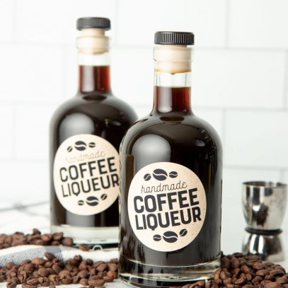 Two bottles of homemade kahlua on a kitchen counter surrounded by coffee beans.