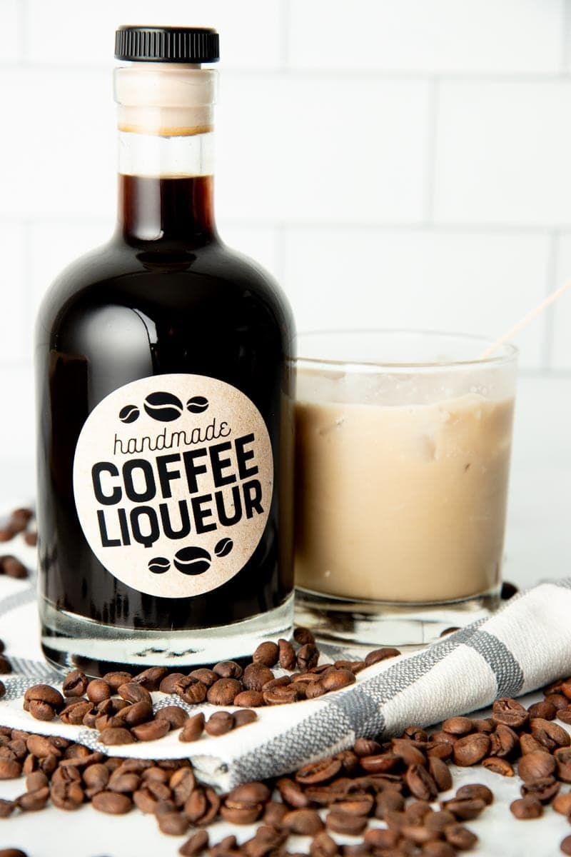 A bottle of homemade coffee liqueur stands next to a mixed white russian cocktail.