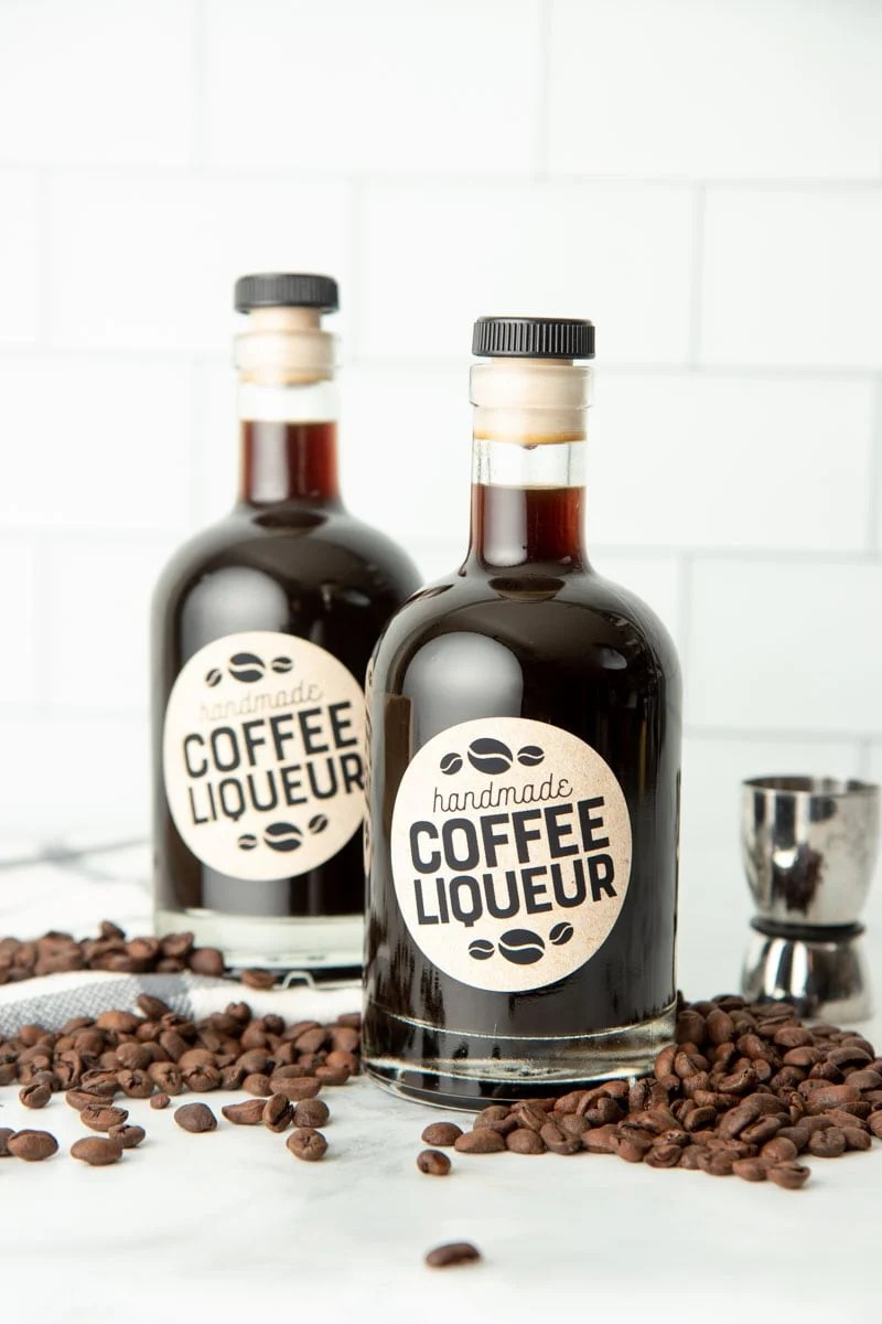 Two bottles of homemade kahlua on a kitchen counter surrounded by coffee beans. Liqueurs like this make great Christmas food gifts!