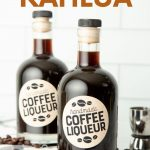 "Two bottles of homemade kahlua on a kitchen counter surrounded by coffee beans. A text overlay reads, ""Homemade Kahlua."""