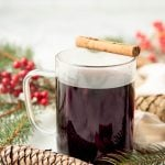 A mug of Christmas wassail sits with a cinnamon stick balanced across the rim.