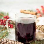 A mug of Christmas wassail sits with a cinnamon stick balanced across the rim.