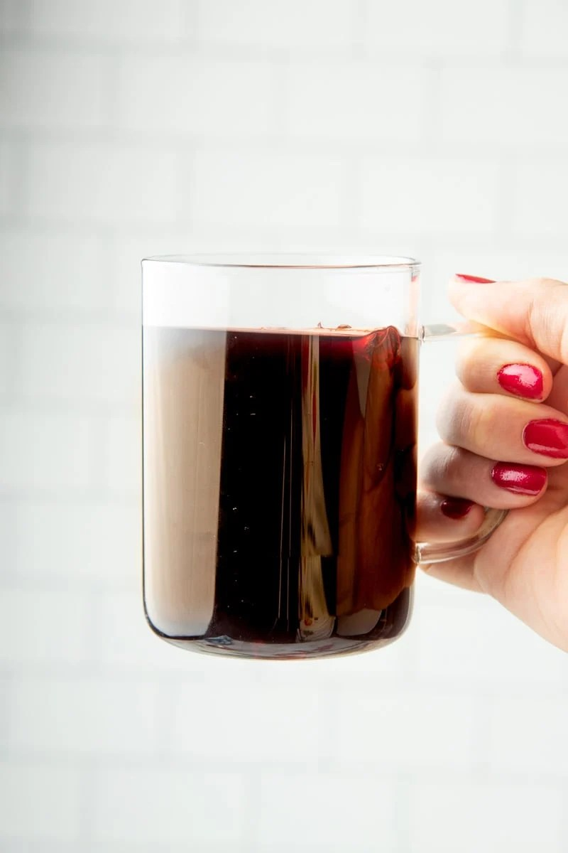 Hand holding up a mug of mulled wine by the handle.