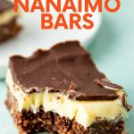 "Close-up of a nanaimo bar with a bite taken out of it. A text overlay reads, ""Classic Canadian Nanaimo Bars."""