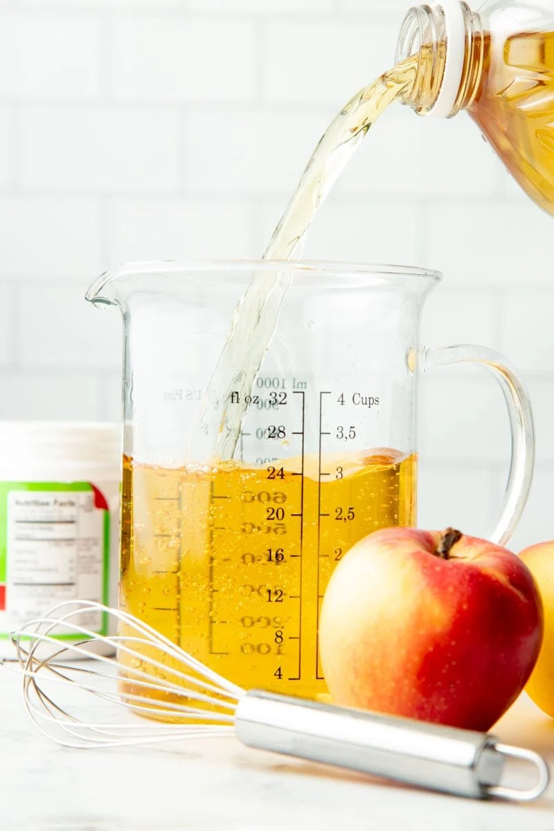 Pouring apple juice into a four-cup, glass measuring cup.