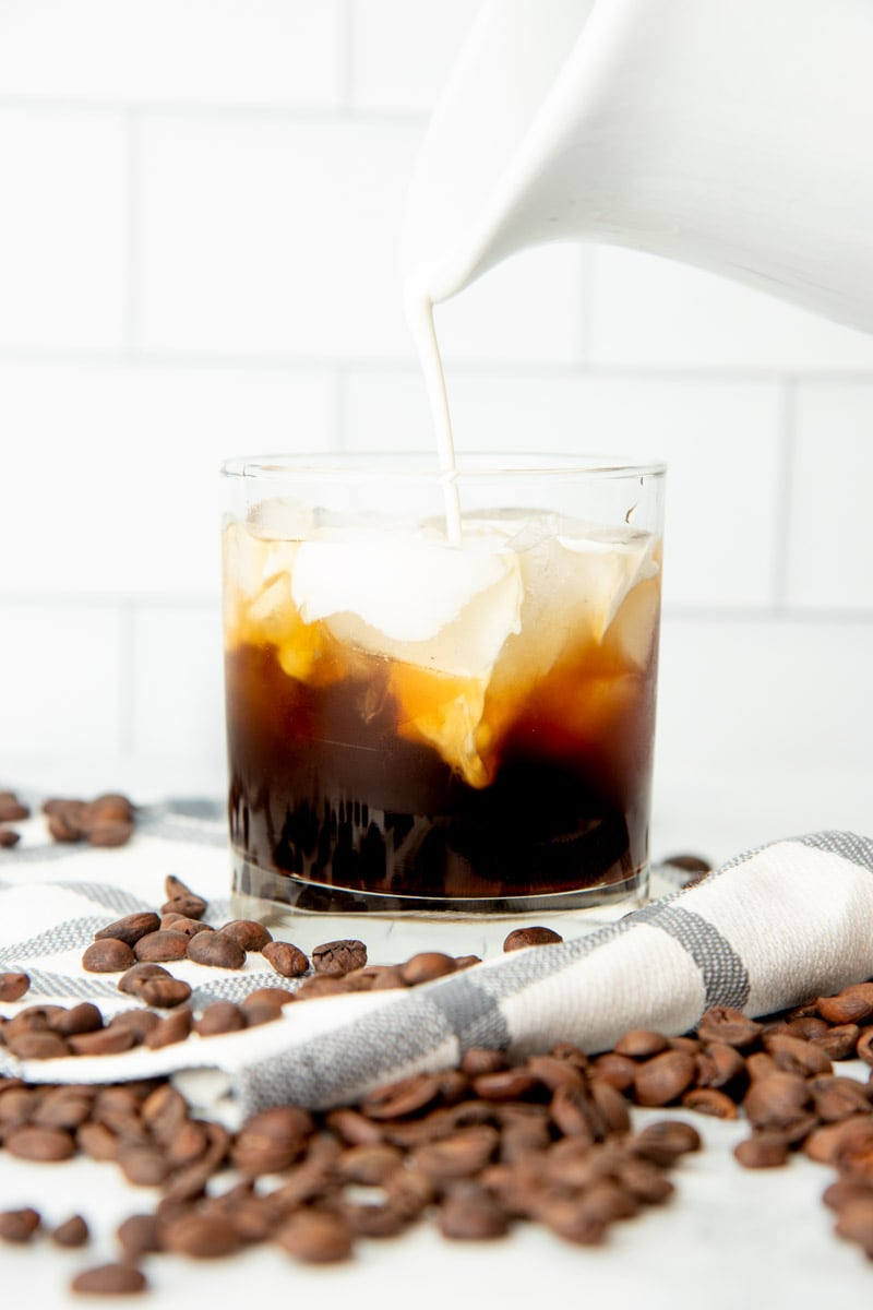 Pouring cream into a rocks glass filled with homemade coffee liqueur, vodka, and ice.