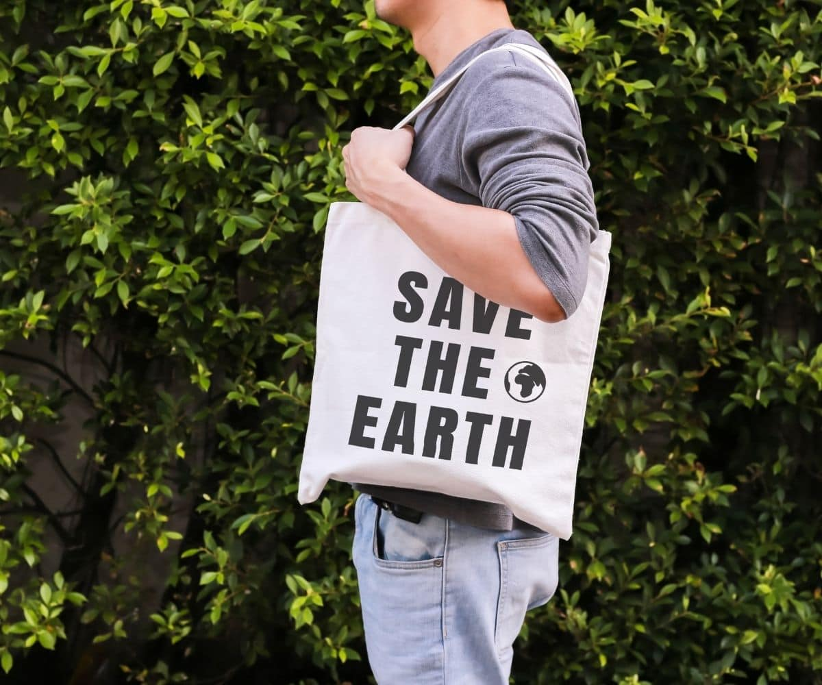 A man standing in profile with a Save the Earth tote over his shoulder.