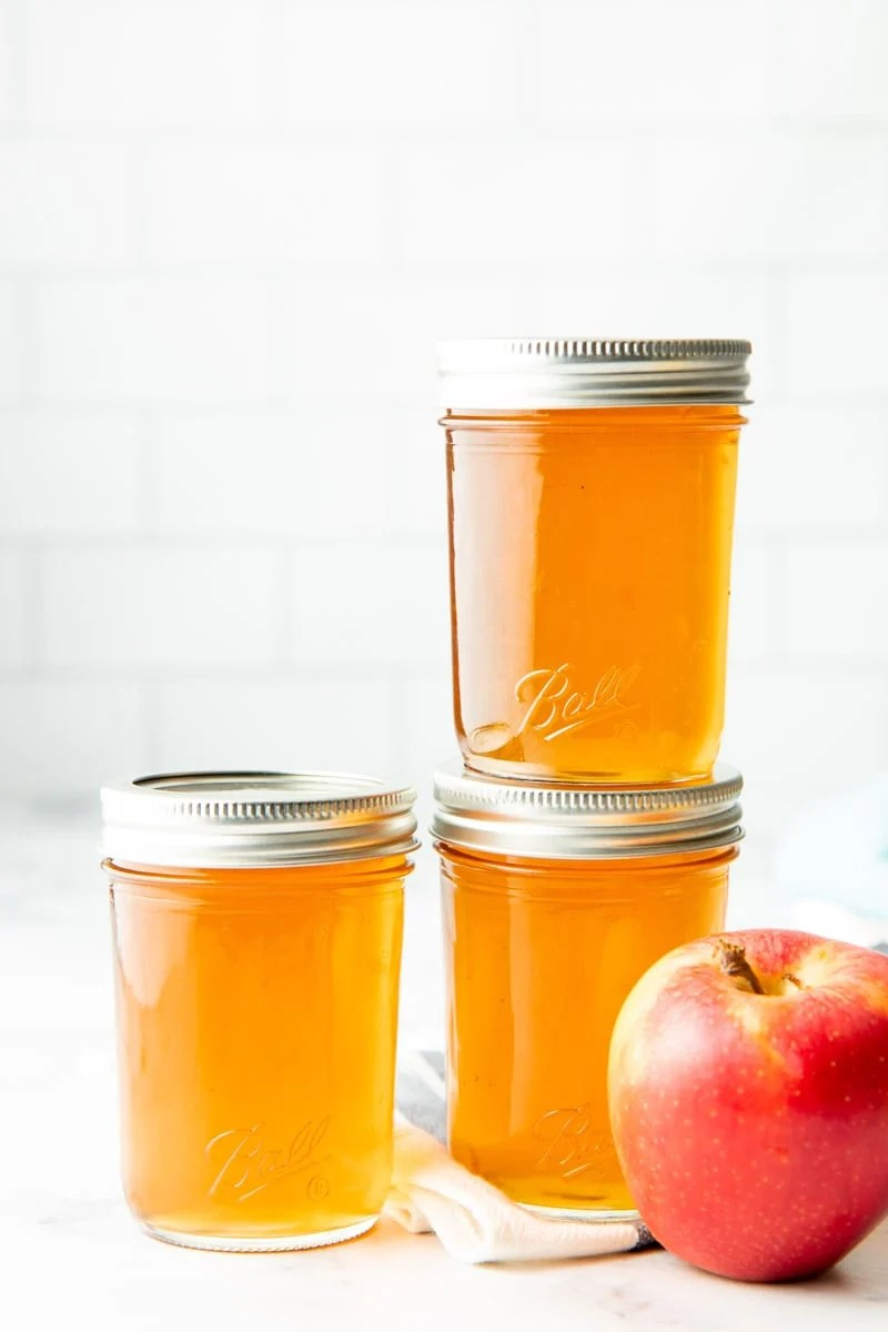 Three pint-sized jars of apple jelly stacked next to a fresh apple.