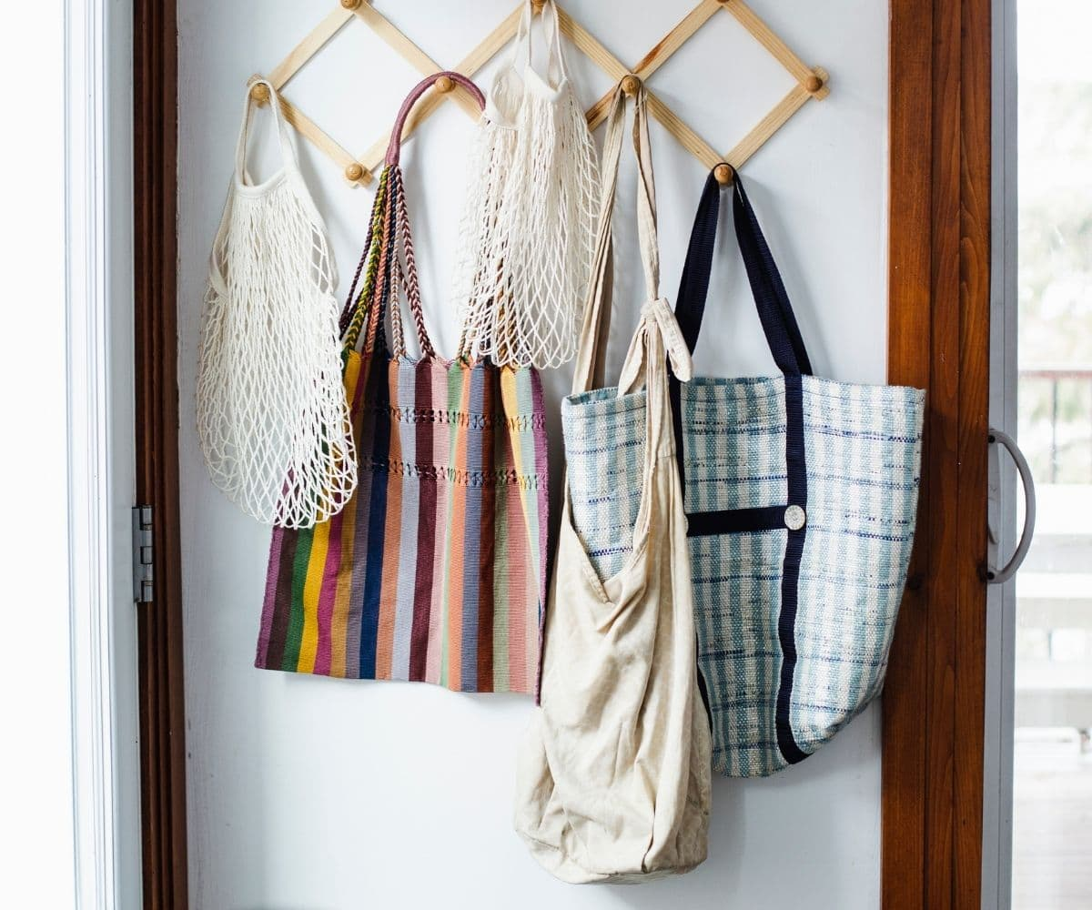 Various style of reusable tote bags hanging on wooden pegs by the door.