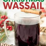 "A mug of Christmas wassail sits with a cinnamon stick balanced across the rim. A text overlay reads, ""Secret Family Recipe! Christmas Wassail."""