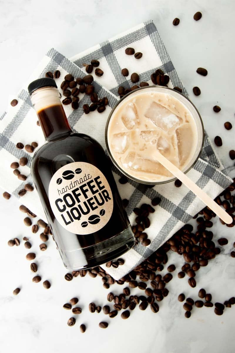 Overhead of a bottle of homemade coffee liqueur lying beside a white russian on the rocks.