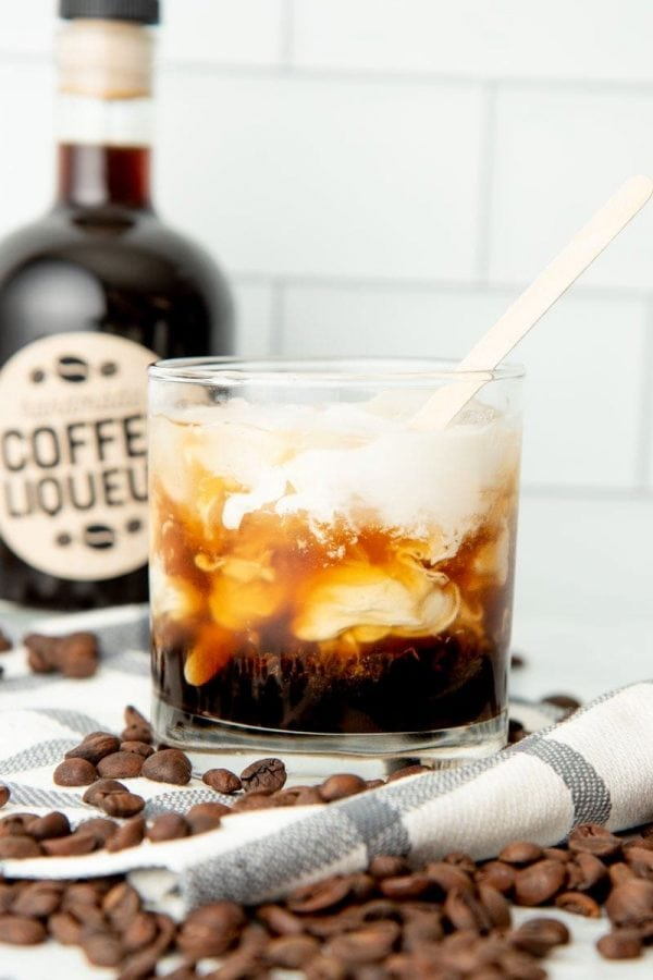 A wooden stirrer mixes a tumbler filled with homemade kahlua, vodka, and cream into a white russian drink.
