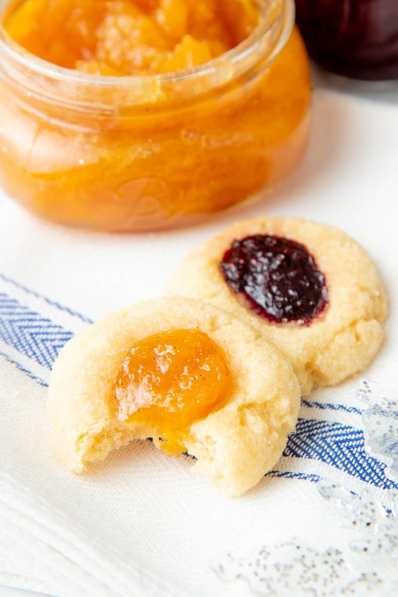 Close-up of a jam thumbprint cookie with a bite out of it sitting in front of another cookie and an open jar of jam.
