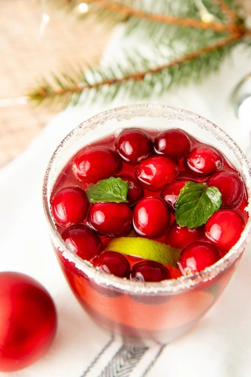 Close-up of the top of a glass of punch garnished with cranberries, limes, and mint.
