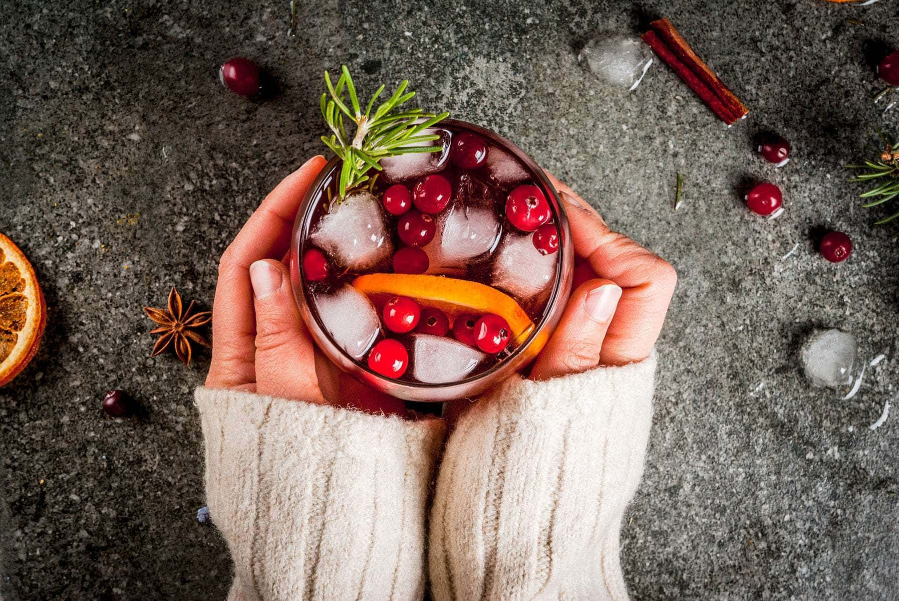 Top view of two hands holding a festive christmas cocktail garnished with cranberries, an orange slice, and a rosemary sprig.