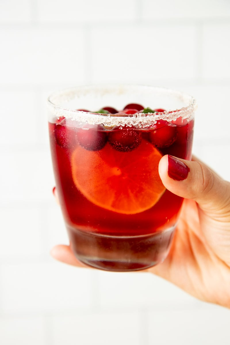 A hand holds up a glass of Christmas punch with fresh garnishes and a sugar rim.