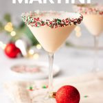 "A Christmas martini stands on a kitchen linen surrounded by holiday decor. A text overlay reads, ""Sugar Cookie Martini."""