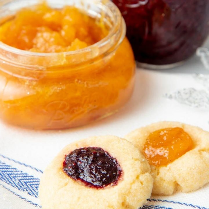 Close-up of two jam thumbprint cookies with open jars of homemade jam behind them.