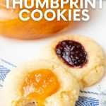 """Close-up of two cookies in front of an open jar of jam. A text overlay reads, """"Shortbread Thumbprint Cookies."""""""