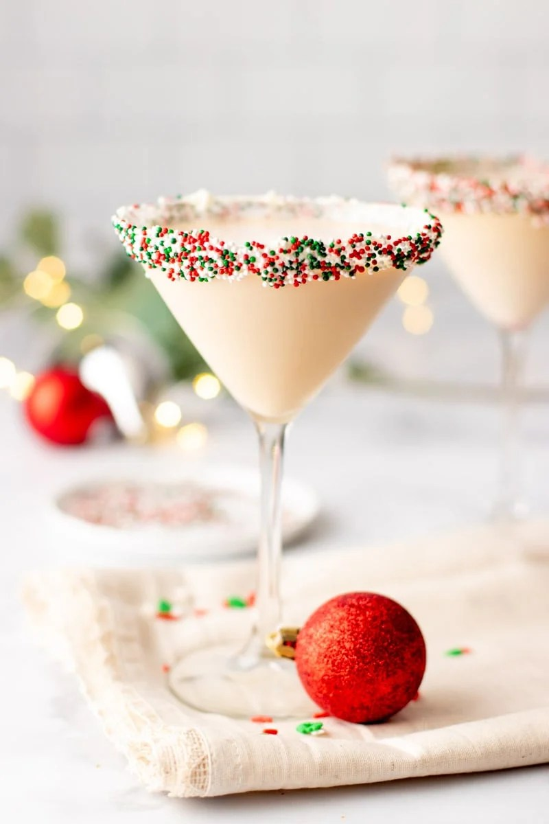 A Christmas martini stands on a kitchen linen surrounded by holiday decor.