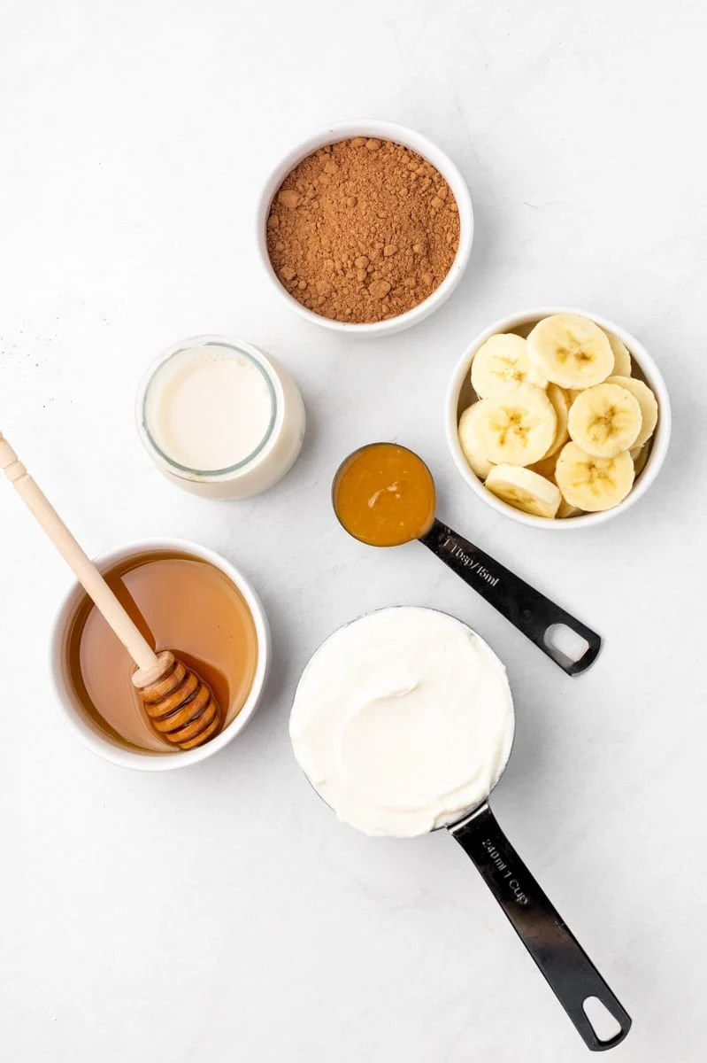 Overhead of the ingredients needed to make a chocolate peanut butter smoothie.