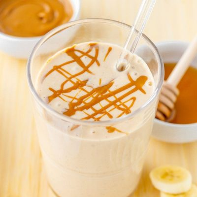 Close-up of finished smoothie with peanut butter drizzle and fresh ingredients around it.