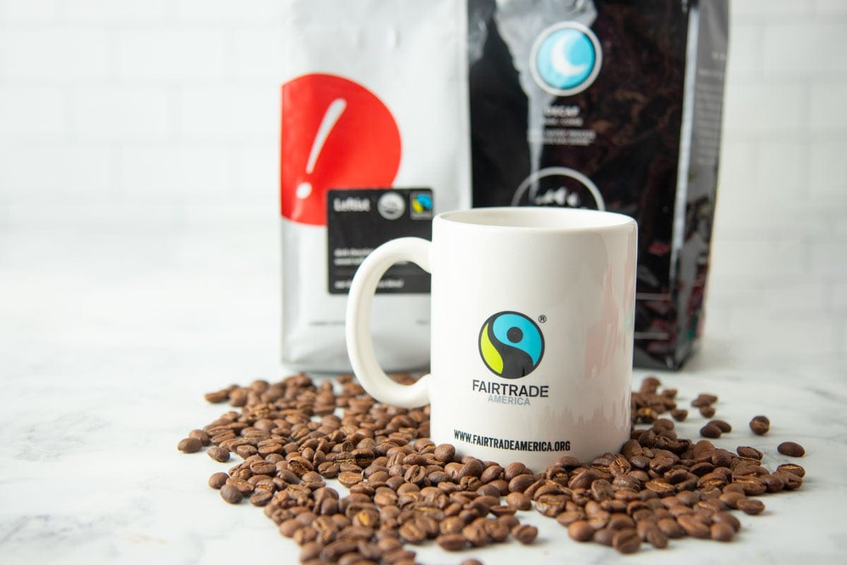 A mug with the Fairtrade America logo on it sits on a bed of coffee beans, in front of some bags of fairtrade coffee.