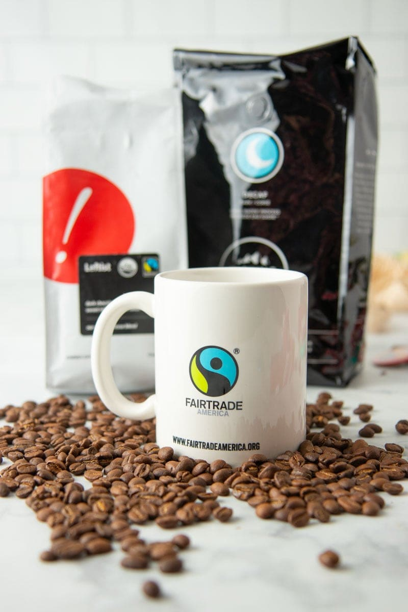 A mug with the Fairtrade America logo on it sits on a bed of coffee beans.