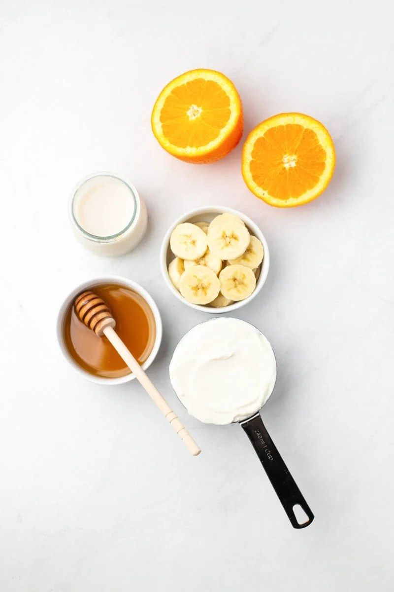 Overhead of the five ingredients needed to make an orange smoothie.