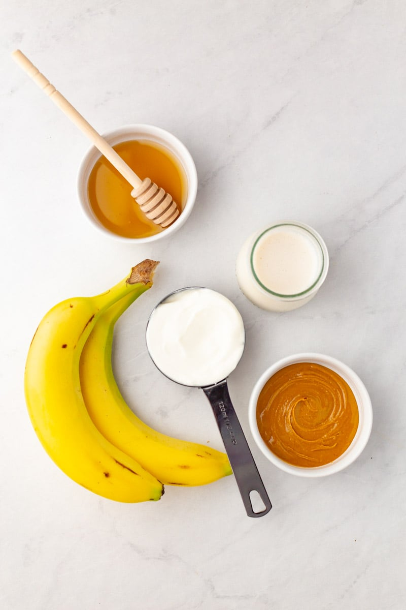 Overhead of the five ingredients needed to make a peanut butter banana smoothie.