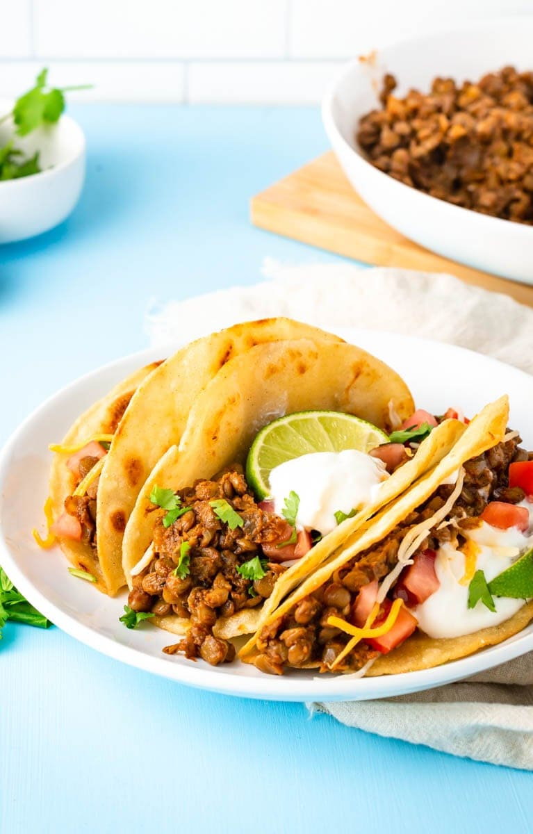 Lentil taco meat spilling out of three tacos plated on a blue counter.